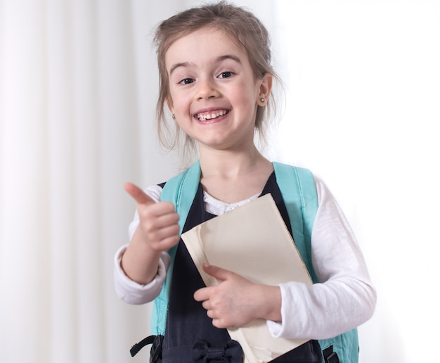 Meisje-basisschool student met een rugzak en een boek Gratis Foto