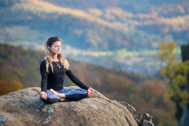 Meisje beoefent yoga en doet asana siddhasana op de top van de berg Premium Foto