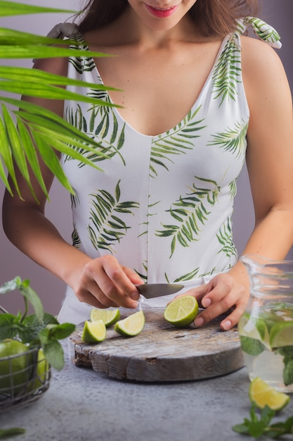 Meisje bereidt zomer limonade snijdt citroen op het bord Premium Foto