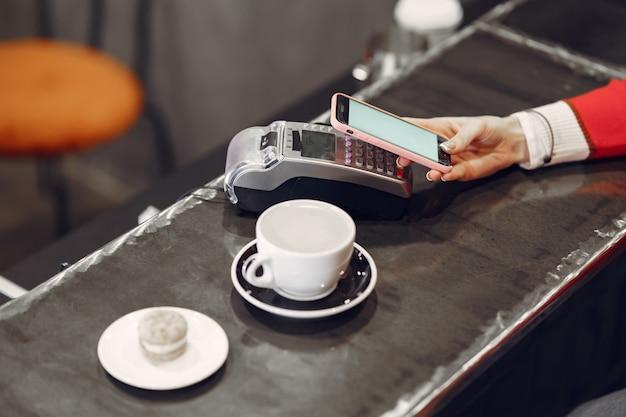 Meisje betaalt voor haar latte met een smartphone door contactloze pay pass-technologie Gratis Foto