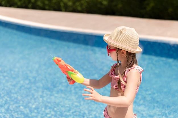Meisje bij pool het spelen met waterkanon Gratis Foto