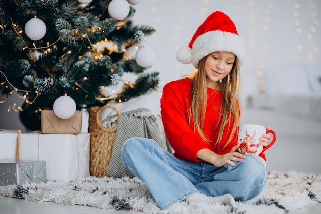 Meisje cacao drinken door kerstboom Gratis Foto