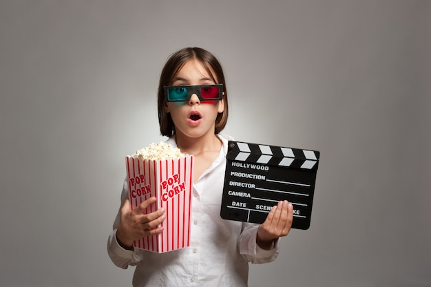 Meisje dat 3d-bril draagt en popcorn eet Premium Foto