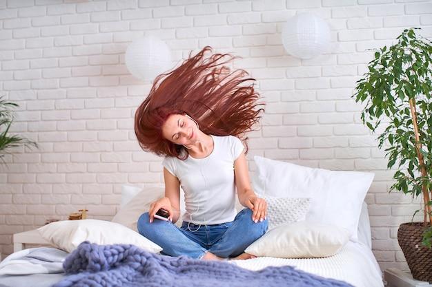 Meisje dat aan muziek in hoofdtelefoons op het bed luistert. roodharig jong mooi meisje in jeans en t-shirt gelukkig in koptelefoon luisteren naar muziek en dansen ontwikkelt haar. Premium Foto