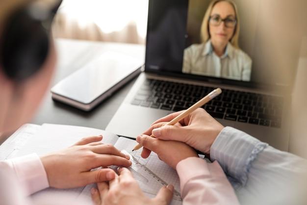 Meisje dat aantekeningen maakt terwijl het hebben van een online klasse Gratis Foto