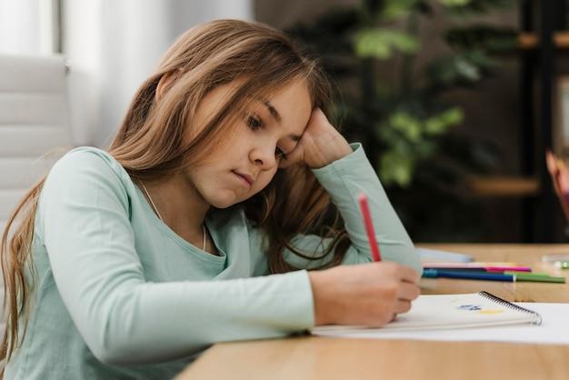 Meisje dat aantekeningen maakt terwijl ze zich thuis verveelt Gratis Foto