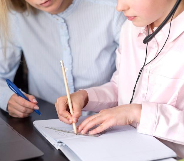 Meisje dat aantekeningen naast leraar maakt Gratis Foto