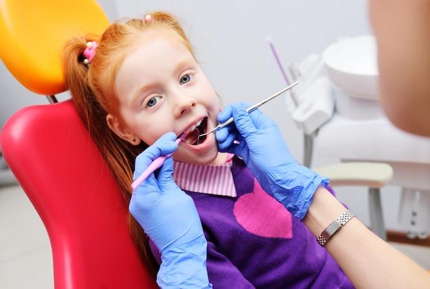 Meisje dat als rode tandvoorzitter glimlacht. de tandarts onderzoekt de tanden van de patiënt van het kind. kindertandheelkunde Premium Foto
