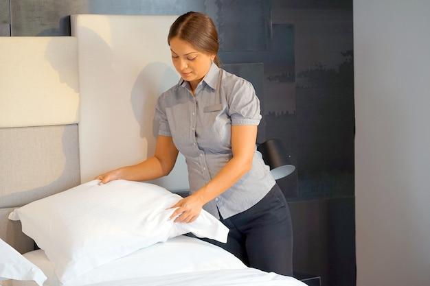 Meisje dat bed in hotelkamer maakt. huishoudster bed opmaken Premium Foto