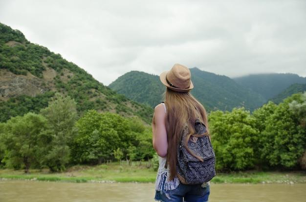 Meisje dat de groene bergen en de rivier bewondert Premium Foto