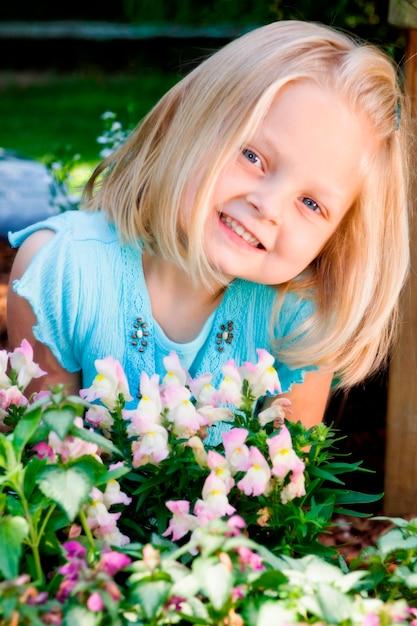 Meisje dat door bloemen, portret glimlacht Premium Foto