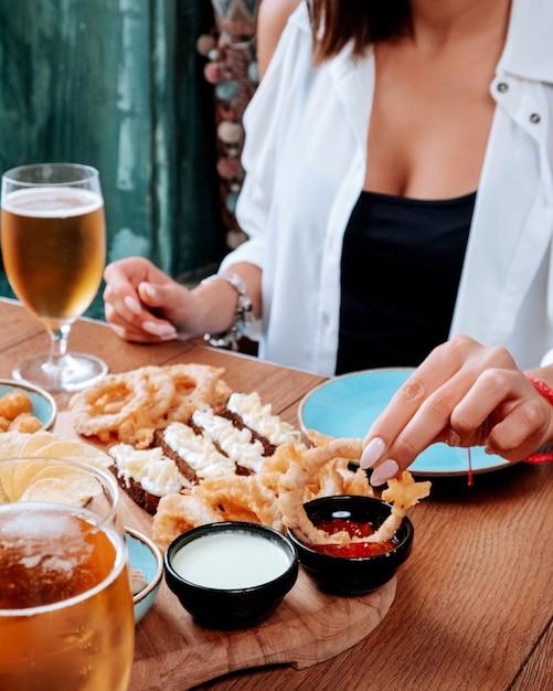 Meisje dat een bierreeks eet en bier met schuim drinkt Gratis Foto
