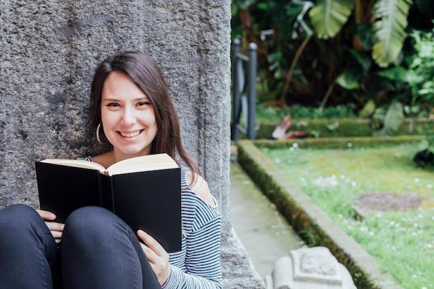 Meisje dat een boek in de straat leest Gratis Foto