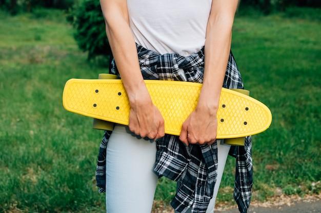Meisje dat een geel plastic skateboard in het park houdt Premium Foto