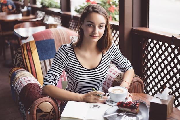 Meisje dat een kop van koffie in het notitieboekje trekt Gratis Foto