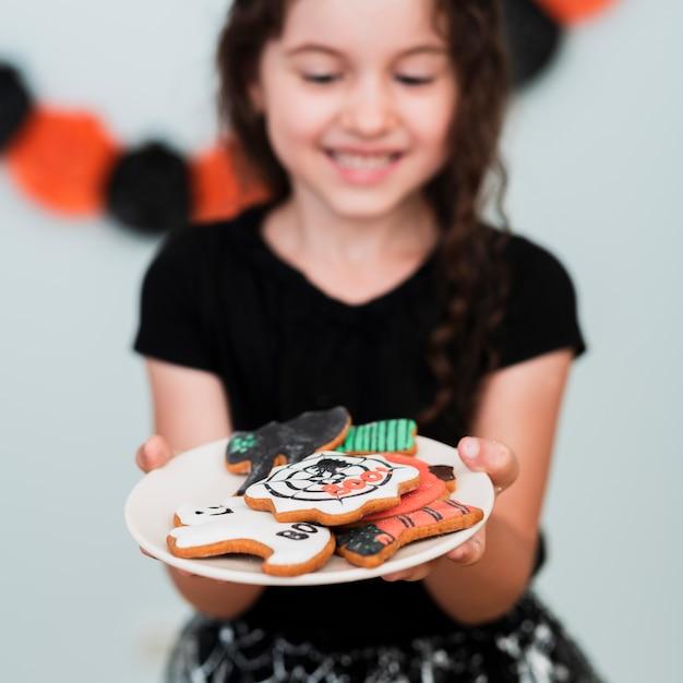 Meisje dat een plaat met koekjes houdt Gratis Foto