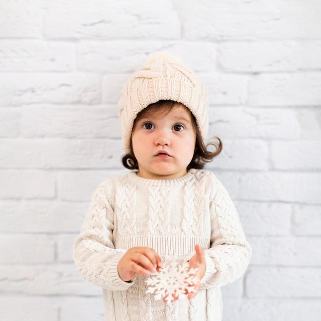 Meisje dat een sneeuwvlok houdt en fotograaf bekijkt Gratis Foto