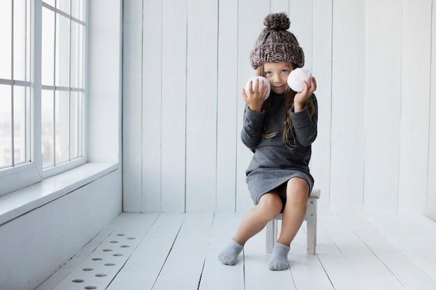 Meisje dat en sneeuwballen zit houdt Gratis Foto
