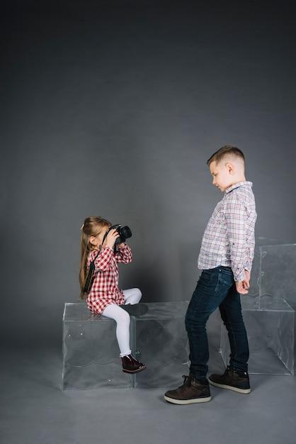 Meisje dat foto van een jongen met camera neemt tegen grijze achtergrond Gratis Foto