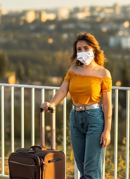Meisje dat gezichtsmasker met koffer in park draagt. reizen tijdens pandemie Premium Foto