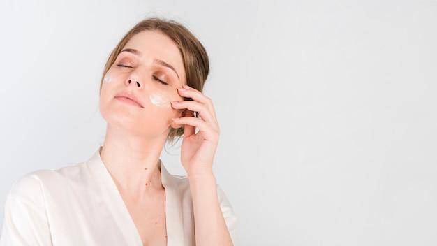 Meisje dat haar cosmetisch product toepast Gratis Foto
