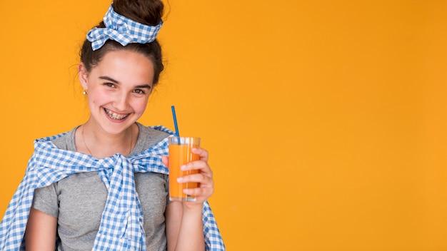 Meisje dat haar jus d'orange met exemplaarruimte houdt Gratis Foto