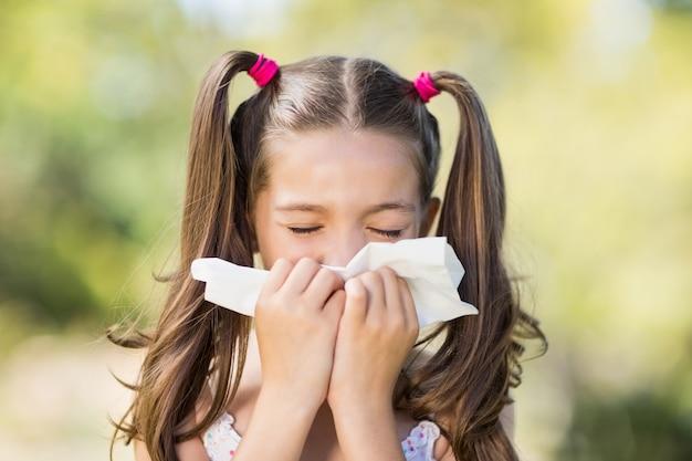 Meisje dat haar neus met zakdoek blaast terwijl het niezen Premium Foto