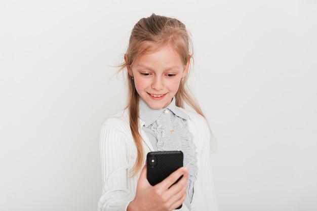 Meisje dat haar smartphone bekijkt Gratis Foto