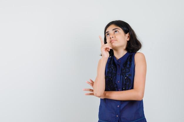 Meisje dat in blauwe blouse benadrukt en nieuwsgierig kijkt. Gratis Foto