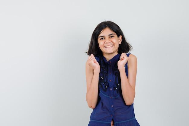 Meisje dat in blauwe blouse winnaargebaar toont en blij kijkt Gratis Foto