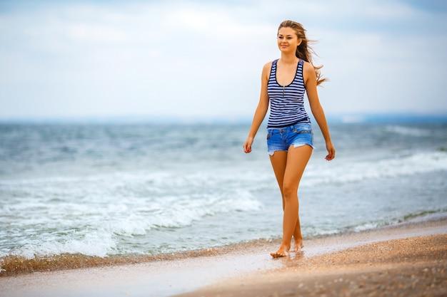 Meisje dat in borrels op het strand loopt Premium Foto
