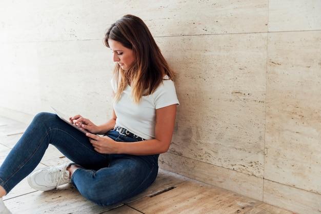 Meisje dat in jeans moderne tablet controleert Gratis Foto