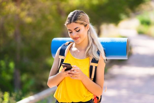 Meisje dat in openlucht wandelt die een bericht met mobiel verzendt Premium Foto