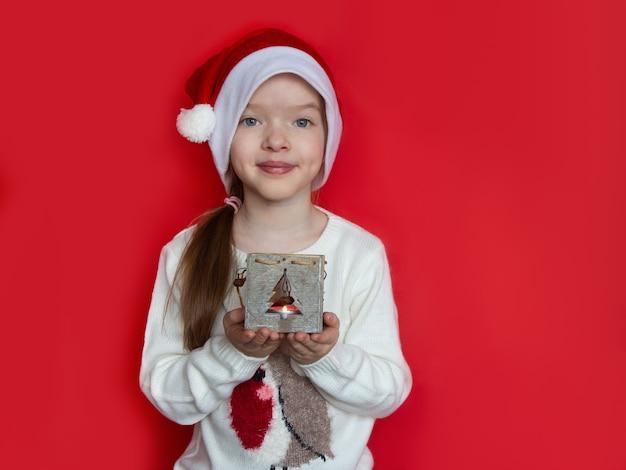 Meisje dat in santahoed de kandelaar van kerstmis houdt Premium Foto