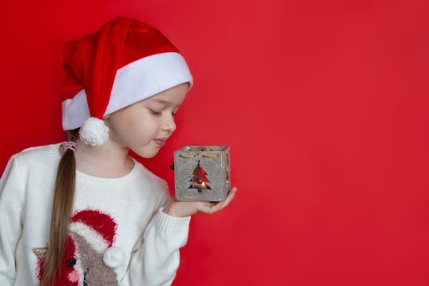 Meisje dat in santahoed een concept van het kandelaarnieuwjaar en kerstmis houdt Premium Foto