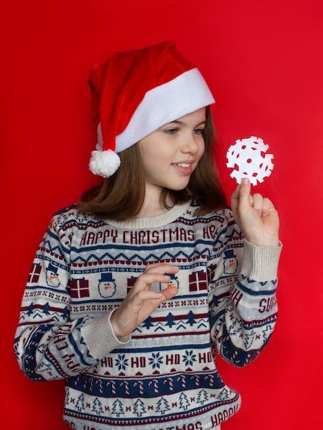 Meisje dat in santahoed een sneeuwvlok nieuw jaar en kerstmisconcept houdt Premium Foto