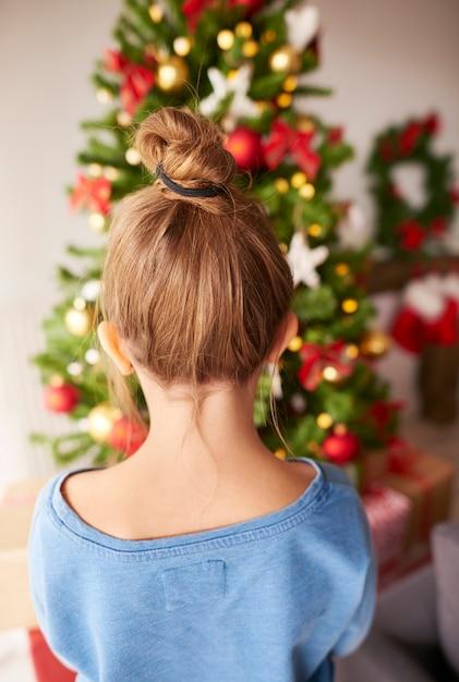 Meisje dat kerstboom bekijkt Gratis Foto