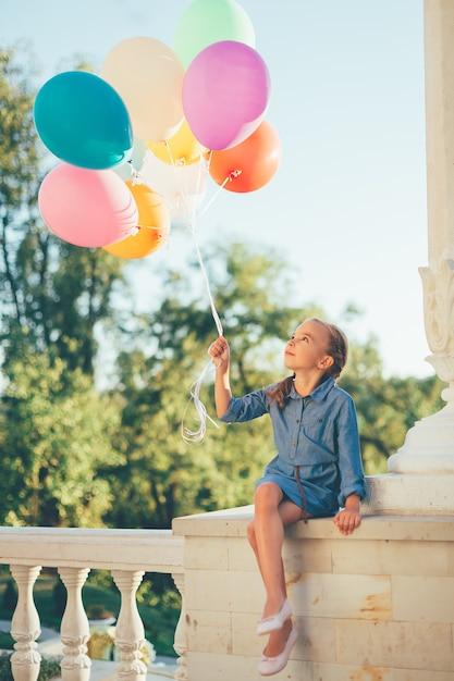 Meisje dat kleurrijke ballons houdt kijkend aan hen Gratis Foto