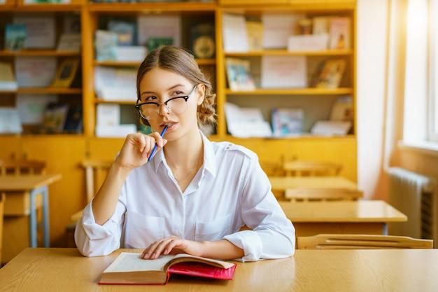 Meisje dat met glazen bij een lijst met een boek in het klaslokaal zit Premium Foto