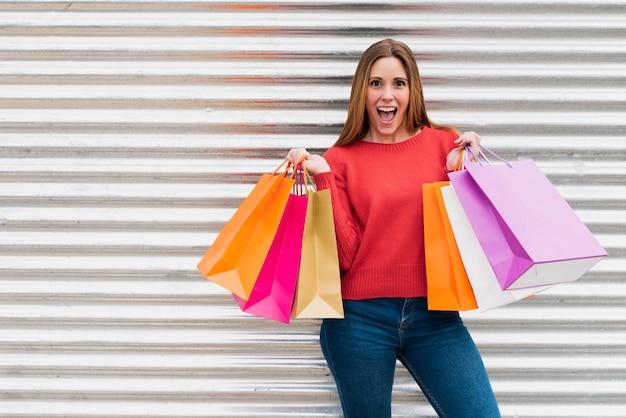Meisje dat met het winkelen zakken camera bekijkt Gratis Foto