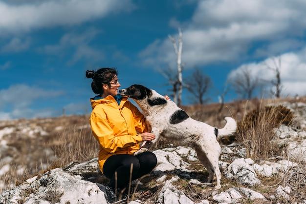 Meisje dat met hond in de bergen loopt. hondenvriend. lopen met je huisdier. reizen met een hond. een huisdier. slimme hond. beste vriendin. de hond likt zijn gezicht. Premium Foto