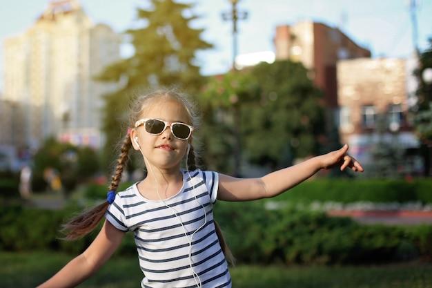 Meisje dat met hoofdtelefoon in de straat danst Premium Foto