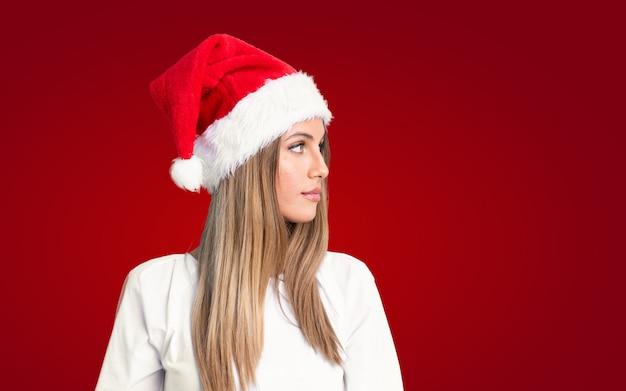 Meisje dat met kerstmishoed aan de kant kijkt Premium Foto