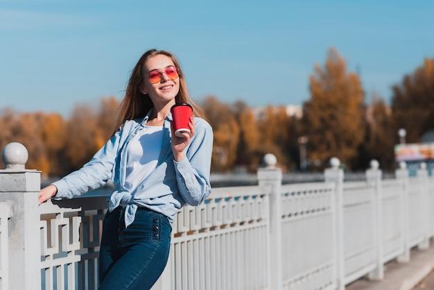 Meisje dat met zonnebril een kop van koffie houdt Gratis Foto
