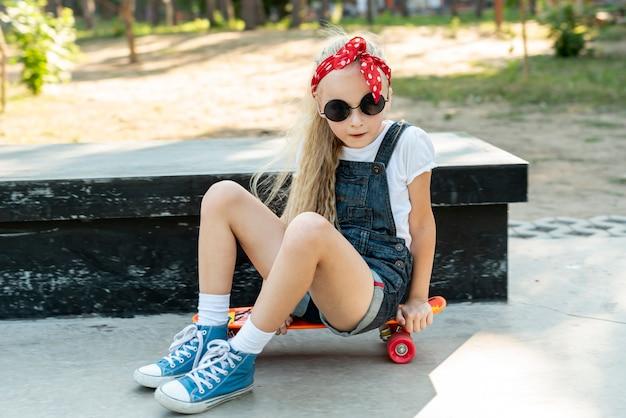 Meisje dat met zonnebril op skateboard zit Gratis Foto