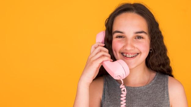 Meisje dat op een roze telefoon met exemplaarruimte spreekt Gratis Foto