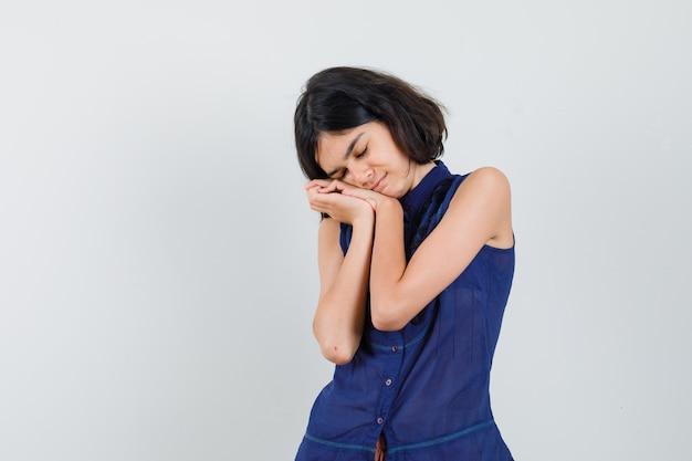 Meisje dat op handen als hoofdkussen in blauwe blouse leunt en leuk kijkt. Gratis Foto