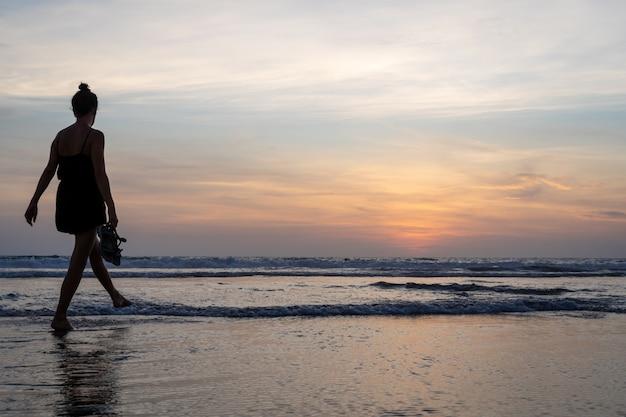 Meisje dat op het water op een strand loopt Gratis Foto