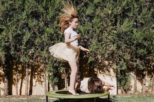 Meisje dat op trampoline springt dichtbijgelegen zuster Gratis Foto