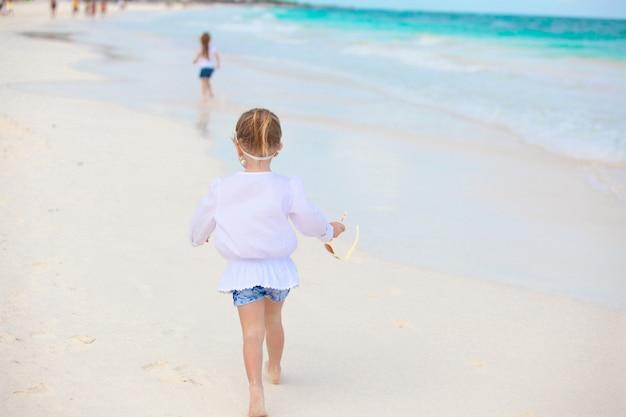 Meisje dat op wit zandig strand in mexico loopt Premium Foto